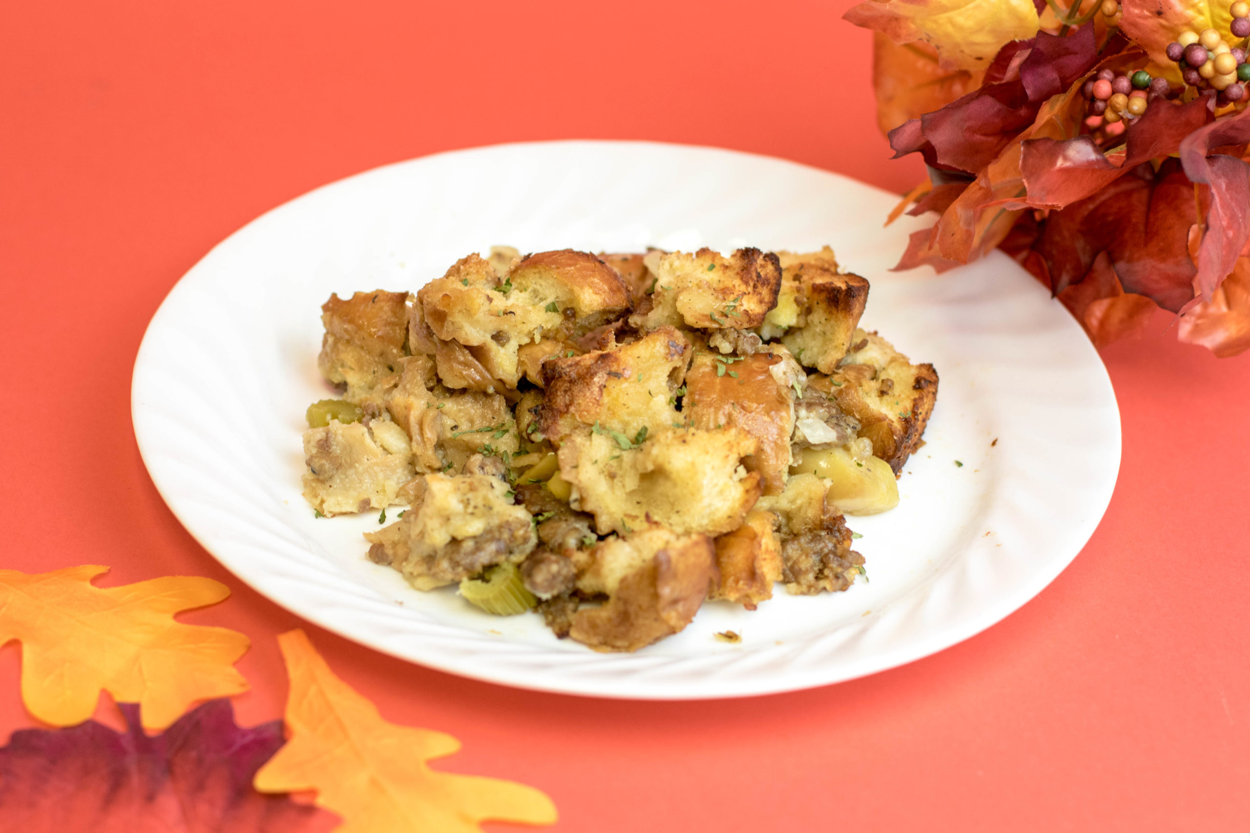 Thanksgiving stuffing on a white plate surrounded by fall leaves sitting on a red background.