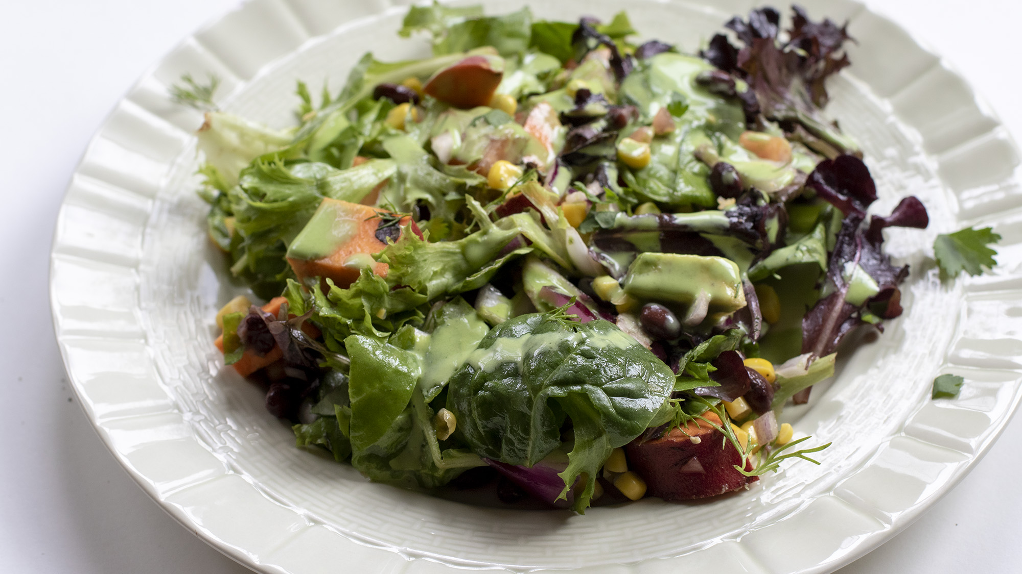 Southwestern salad with dressing on a green plate on a white background.